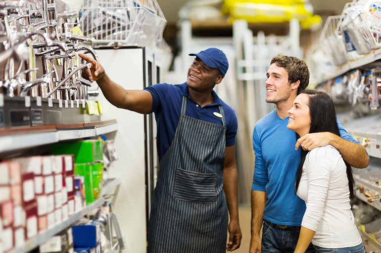 A young couple is receiving water saving tips from a hardware store clerk