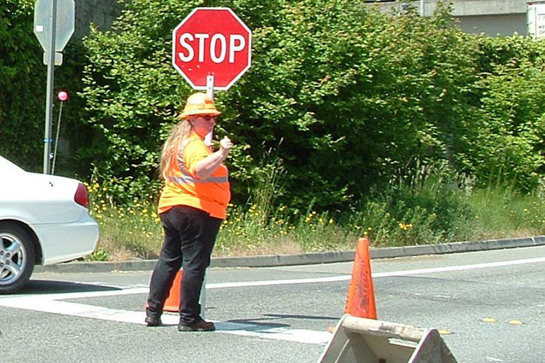 Construction flagger in roadway holding a stop sign