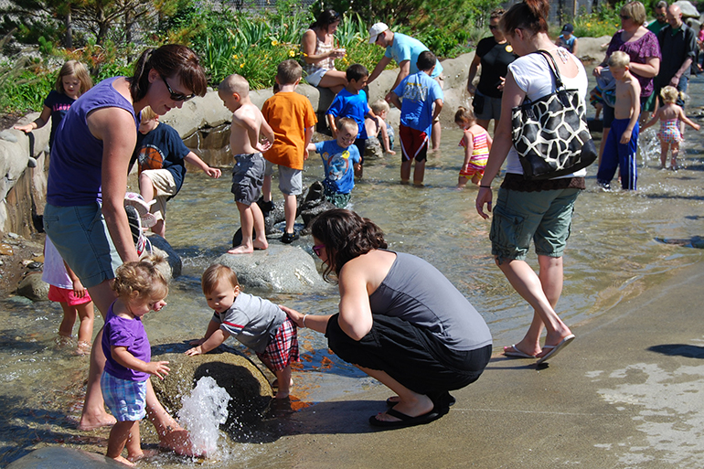 Children and adults playing in the reclaimed water stream at the East Bay Public Plaza