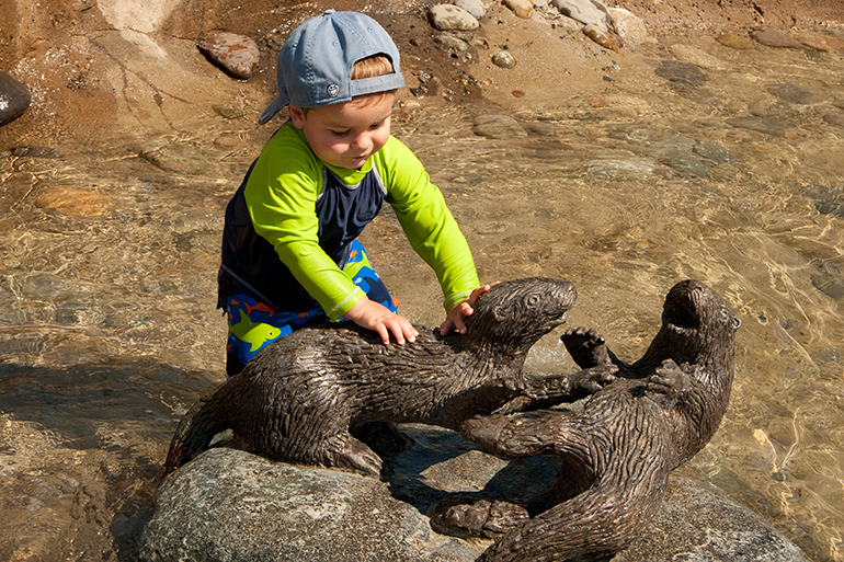 Young boy playing on a bronze otter sculpture in the East Bay Public Plaza reclaimed water stream