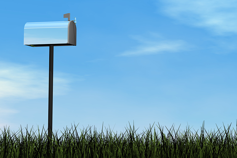 White mailbox with a vast blue sky and grass in the foreground