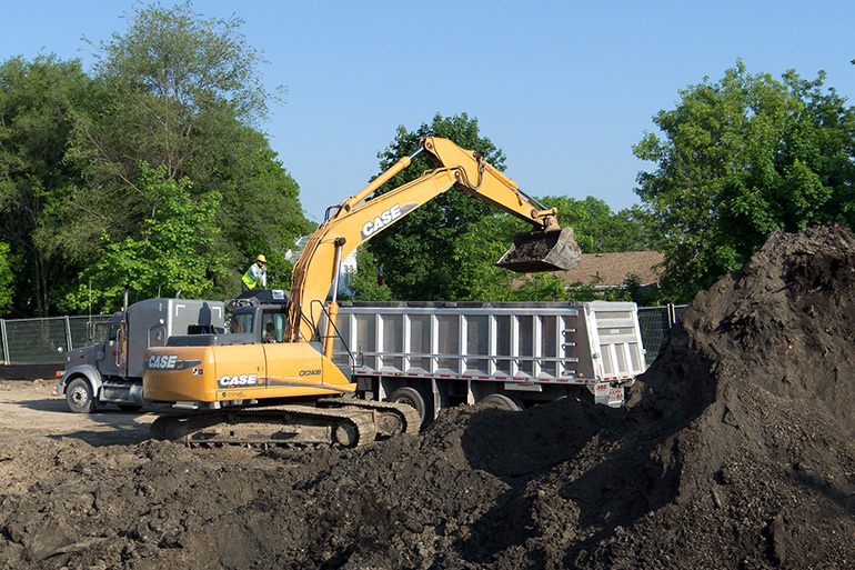 Large construction excavator removes soil from a development site and loads it into a large truck