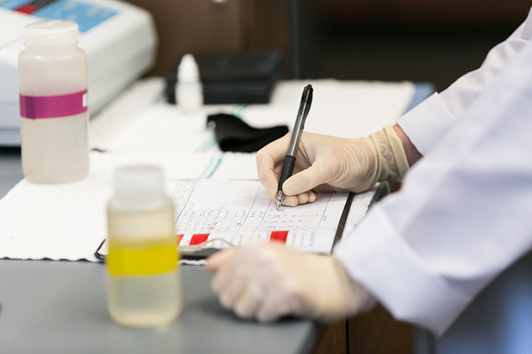 Lab assistant recording water test results in a notebook