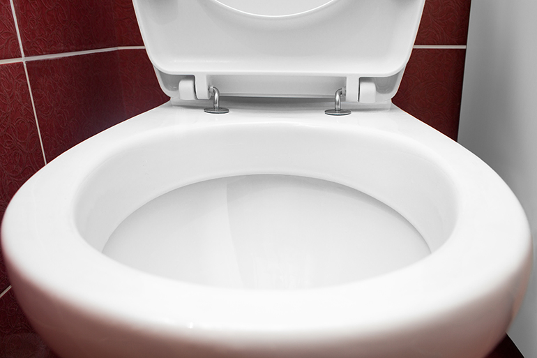 Close-up view of a toilet with tile background.