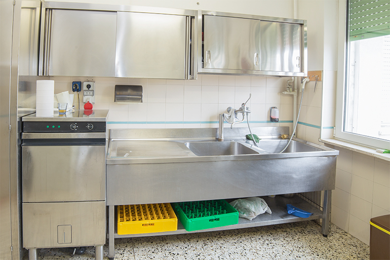 A large industrial kitchen with refrigerator, dishwasher and sink all stainless steel